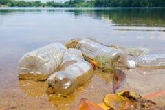 Slechte milieugewoonte van ongepaste verwijdering van de niet biologisch afbreekbare koppen en de flessen van pvc in een meer Sel stock foto