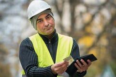 Slechte tijden: slechte bouwvakker en zijn lege portefeuille stock foto