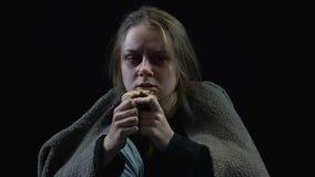 Slechte vrouw omvat in vuile deken die etend korst van brood, armoede, oorlog schreeuwen stock footage