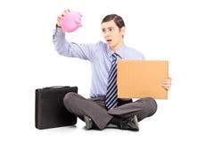 Slechte zakenman die een lege piggybank en een stuk van cardb houden Stock Foto's