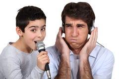 Slechte zanger met vader Stock Foto