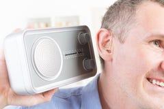 Slechthorende mens die proberen te luisteren radio stock foto's