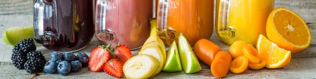 Slection av fruktsafter för ny frukt i krus arkivfoto