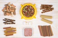 Sélection d'aliments pour chiens sur le fond blanc et en bois Photographie stock