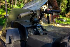 Sled and Cabin in the Woods. A snowmobile sled in the foreground with a wood cabin in the background, in the remote area of Bralorne at summer`s end Stock Photo