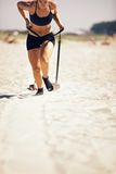 Sled Pull. Female crossfitter pulling a sled on sand during crossfit workout Royalty Free Stock Photo