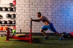 Sled push man pushing weights workout stock image
