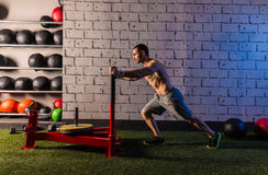Sled push man pushing weights workout. Exercise royalty free stock image