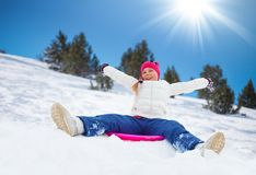 Sled sliding. Happy girl sitting on sled with her hands lifted, wearing ski mask, in the mountains Stock Photo