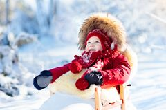 Sled and snow fun for kids. Baby sledding in winter park. Royalty Free Stock Photo