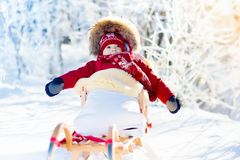 Sled and snow fun for kids. Baby sledding in winter park. Sled and snow fun for kids. Baby sledding in snowy winter park. Little boy in warm red jacket and Royalty Free Stock Photos