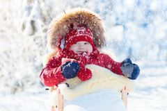 Sled and snow fun for kids. Baby sledding in winter park. Sled and snow fun for kids. Baby sledding in snowy winter park. Little boy in warm red jacket and Stock Photo