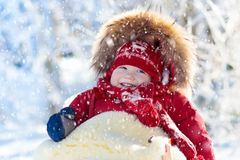 Sled and snow fun for kids. Baby sledding in winter park. Sled and snow fun for kids. Baby sledding in snowy winter park. Little boy in warm red jacket and Stock Image