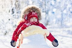 Sled and snow fun for kids. Baby sledding in winter park. Sled and snow fun for kids. Baby sledding in snowy winter park. Little boy in warm red jacket and Stock Images