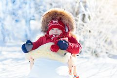 Sled and snow fun for kids. Baby sledding in winter park. Sled and snow fun for kids. Baby sledding in snowy winter park. Little boy in warm red jacket and Royalty Free Stock Photo