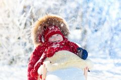 Sled and snow fun for kids. Baby sledding in winter park. Sled and snow fun for kids. Baby sledding in snowy winter park. Little boy in warm red jacket and Royalty Free Stock Photography