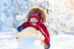 Sled and snow fun for kids. Baby sledding in winter park. Royalty Free Stock Images