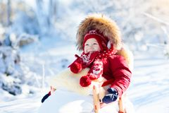 Sled and snow fun for kids. Baby sledding in winter park. Stock Image