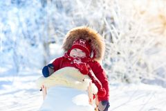 Sled and snow fun for kids. Baby sledding in winter park. Sled and snow fun for kids. Baby sledding in snowy winter park. Little boy in warm red jacket and Stock Photography