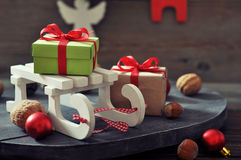 Sled toy with gift boxes. And christmas decorations on wooden background Royalty Free Stock Image