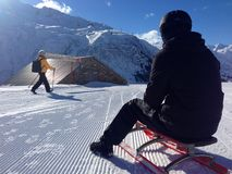 Sledder and walker on the trail in Andermatt, Switzerland. A sledder watches a winter walker on a multi-use trail at the ski resort in Andermatt, Switzerland, on Stock Image