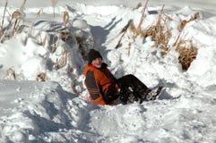 Sledding在多雪的小山下 库存图片