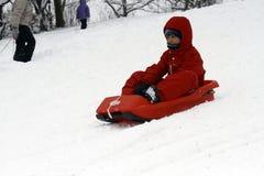 Sledding在小山下在一个冬日 图库摄影