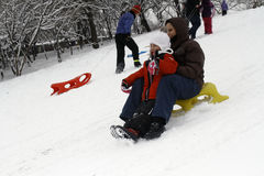 Sledding在小山下在一个冬日 免版税库存图片