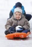 sledding在雪的子项 库存照片