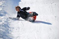 sledding男孩下来落的小山 库存照片
