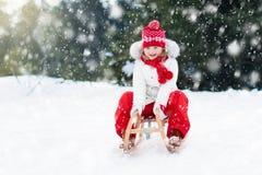 Sledding ребенка Ребенк с розвальнями Потеха снега зимы Стоковая Фотография