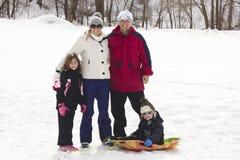 享受天雪sledding的家庭 免版税库存照片