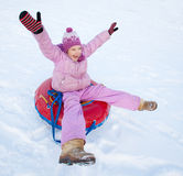 孩子sledding在冬天小山 免版税库存图片