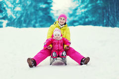 有孩子的妈妈sledding和获得乐趣在冬天 库存图片
