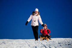 Sledding. Winter activities. A mother and daughter sledding downhill Royalty Free Stock Image
