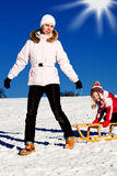 Sledding. Winter activities. A mother and daughter sledding downhill Royalty Free Stock Photos