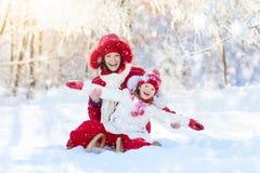 Sledding del bambino e della madre Divertimento della neve di inverno Famiglia sulla slitta immagine stock libera da diritti