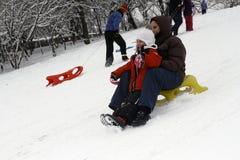 Sledding en bas des collines un jour d'hiver Images libres de droits
