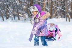 Sledding för två gullig flickor Arkivfoton