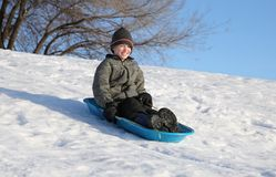 Sledding fun. Happy youth sledding down a snowy hill on a blue sled an smiling Stock Photography