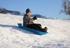 Sledding fun. Happy youth sledding down a snowy hill on a blue sled an smiling Royalty Free Stock Photography