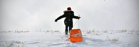 Sledding Fun. Women runs up a sledding hill in Wyomnig Stock Photo