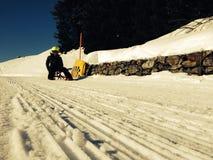 Sledding near Andermatt, Switzerland. A sledder heads down the sledding trail at a ski resort near Andermatt, Switzerland, on a sunny January day Stock Photography