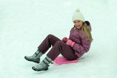 Sledding vestindo do chapéu do inverno da menina meados de da idade Fotografia de Stock Royalty Free