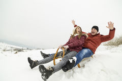 Sledding. Young couple in love sledding down the hill Royalty Free Stock Photos