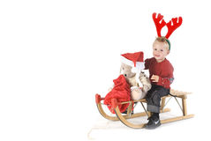 On the sledge. Child with bear on a christmas sledge Royalty Free Stock Image