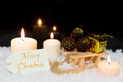 Sledge with presents, candles and a sign in the snow, text merry Stock Images