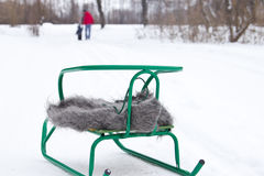 Sledge with a shawl in the snow. Father and son in the distance. Royalty Free Stock Images