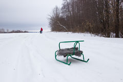 Sledge with a shawl in the snow. Father and son in the distance. Stock Image