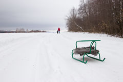 Sledge with a shawl in the snow. Father and son in the distance. Royalty Free Stock Photos